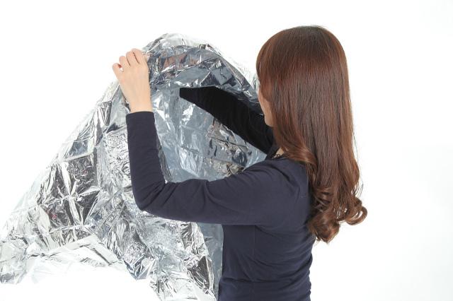 フード付アルミポンチョ(携帯ケース付) フード付きアルミポンチョを着用した女性の後ろ姿の画像