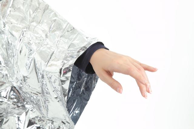 フード付アルミポンチョ(携帯ケース付) フード付きアルミポンチョを着用する女性の姿の画像